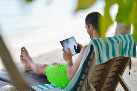 business man relaxing and use tablet computer at beautiful tropical beach